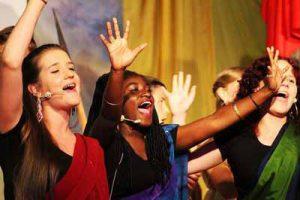Singende Gruppe von Mädchen, die ihre Arme in die Höhe strecken.
